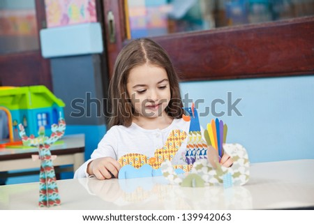 Pretty little preschool girl playing with craft in classroom