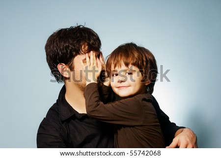 Pretty little smiling boy playing hide-and-seek with his father, studio shot - stock photo