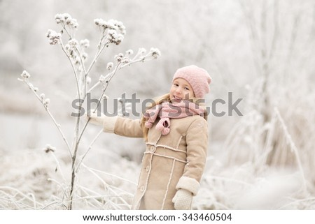pretty little smiling girl with long blond hair in pink knitted hat and scarf and beige coat standing in the white snowy park or forest at winter time - stock photo