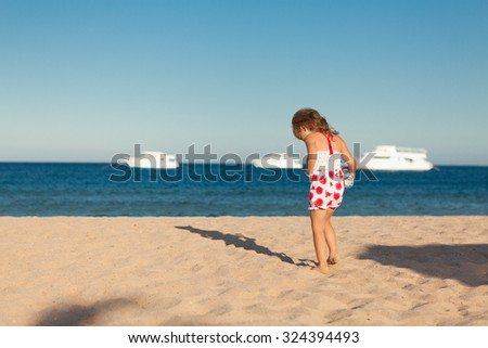 pretty little young girl searching in yellow sea sand