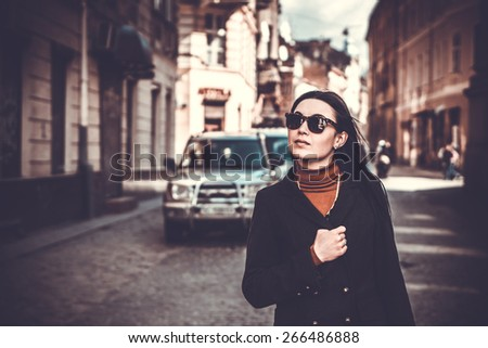 Pretty long hair brunette girl with city street on background - stock photo