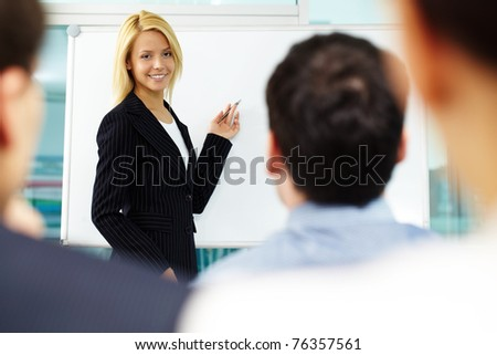 Pretty manager pointing at whiteboard while colleagues listening to her - stock photo