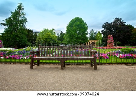 Pretty manicured flower garden with a wooden bench filled with colorful azaleas. - stock photo