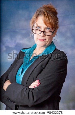 Pretty, mature businesswoman with a thoughtful expression, looking at the camera with her arms crossed across her chest - stock photo