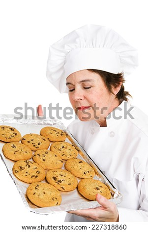 Pretty, mature female chef in her uniform, inhaling the aroma of a tray of her fresh baked chocolate chip cookies.  Isolated on white background - stock photo