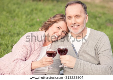 Pretty mature husband and wife are celebrating their anniversary. They are sitting on grass and drinking wine. The man and woman are looking at the camera and smiling - stock photo