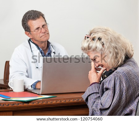 Pretty mature woman consults with her doctor in his office. Focus is on the woman'??s face. She looks worried and tearful. The doctor looks bored and impatient. - stock photo