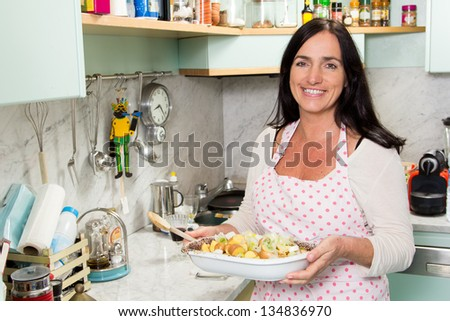 Pretty mature woman cooking in a turquoise kitchen - stock photo