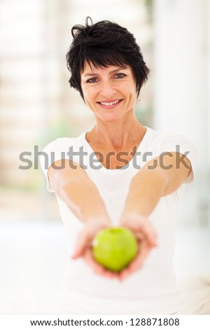 pretty mature woman holding a apple with both hands