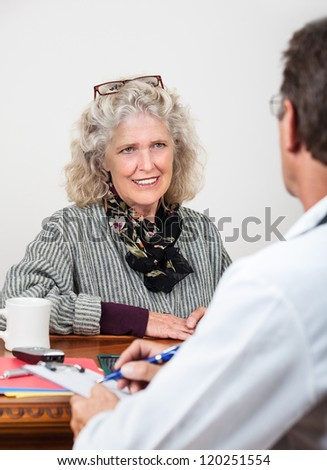 Pretty mature woman patient talks with doctor in his office. Focus on woman. - stock photo