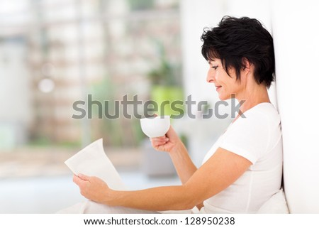 pretty mature woman reading newspaper on bed at home - stock photo