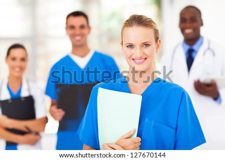 pretty medical nurse and colleagues in hospital - stock photo