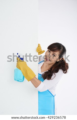 Pretty middle-aged housewife with cleaning spray looking out of the wall