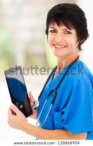pretty middle aged medical doctor with tablet computer in office