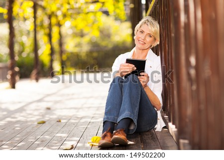 pretty middle aged woman holding tablet computer sitting outdoors - stock photo