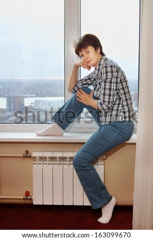 Pretty middle aged woman sits on windowsill