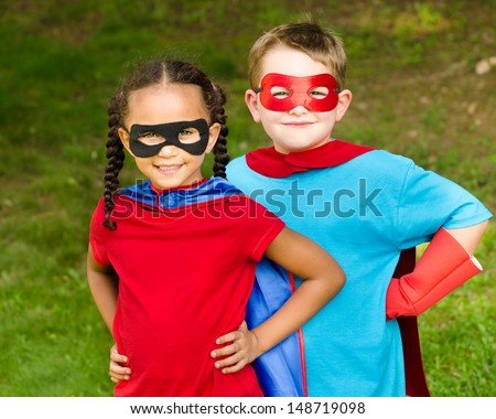 Pretty mixed race girl and Caucasian boy pretending to be superhero - stock photo