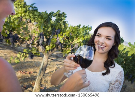 Pretty Mixed Race Young Adult Woman Enjoying A Glass of Wine in the Vineyard with Friends. - stock photo