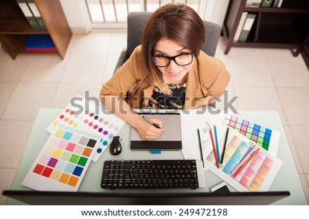 Pretty mixed-raced female designer using a pen tablet and some color swatches for work - stock photo
