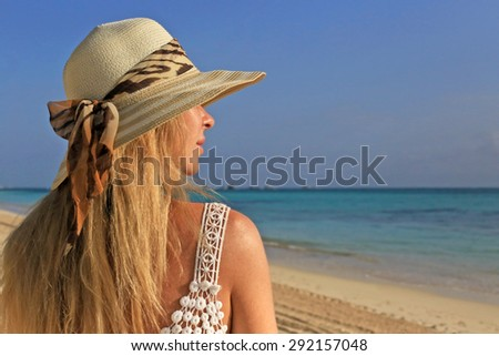 Pretty model in hat relaxing on the evening beach