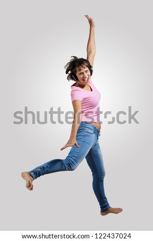 pretty modern slim hip-hop style woman jumping dancing on a grey background - stock photo