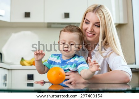 Pretty mom is sitting at the table and holding her child in the kitchen. The orange is lying on the table. A family is looking at it with interest. The woman is smiling with joy - stock photo