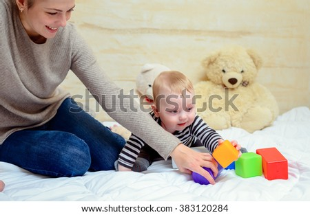 Pretty Mom with her Cute Baby Boy Playing Colored Plastic Toys at Home Together. - stock photo