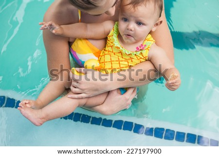 Pretty mother and baby at the swimming pool at the leisure center