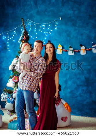 Pretty mother and father pose with their funny little girls before a Christmas tree