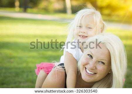 Pretty Mother and Little Girl Having Fun Together in the Grass. - stock photo
