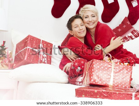 Pretty mother having fun with son. Christmas time. Happiness content. Photo at home, bedroom. Christmas decorations.