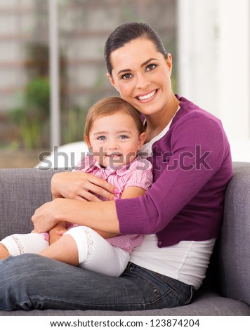 pretty mother hugging cute little daughter on sofa