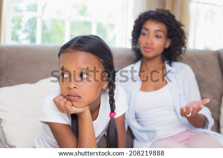 Pretty mother sitting on couch after an argument with daughter at home in the living room - stock photo