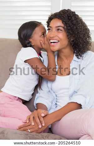 Pretty mother sitting on the couch with her daughter whispering a secret at home in the living room - stock photo