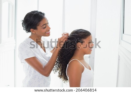 Pretty mother tying her daughters hair back at home in bathroom - stock photo
