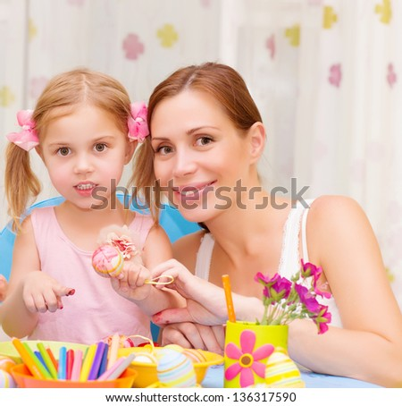 Pretty mother with cute little daughter painted Easter eggs at home, having fun indoor, spring holiday