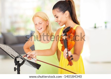 pretty music teacher pointing notes to her student - stock photo