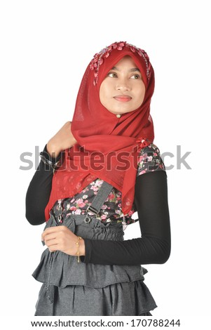 Pretty Muslim girl wearing red head scarf looking around, isolated white