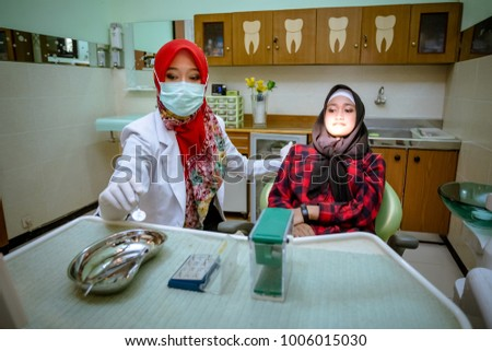 Pretty muslim woman dentist from Indonesia pose in her clinic with her patient