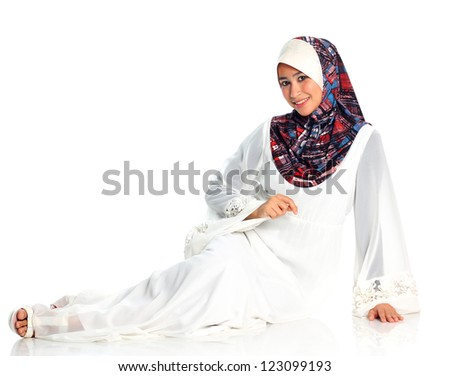 Pretty muslim woman model in action sitting on the floor, on white background