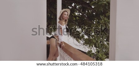 Pretty naturally looking woman on summer day in boho style fashion wearing white shirt, bikini and hat posing on a terrace