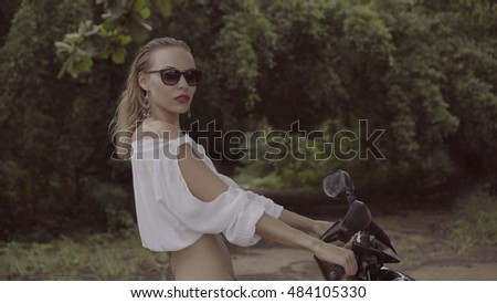 Pretty naturally looking woman on summer day in boho style fashion wearing white shirt, bikini and sunglasses on scooter over green leaves trees background