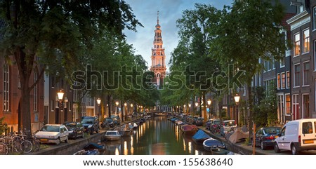 Pretty night reflections and illuminated church spire in the tranquil canals of Amsterdam, Holland. - stock photo