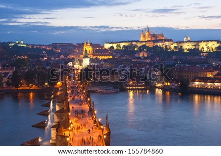 Pretty night time illuminations of Prague Castle, Charles Bridge and St Vitus Cathedral reflected in the Vltava river running through the heart of the city. - stock photo