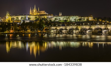 Pretty night time illuminations of Prague Castle, Charles Bridge and St Vitus Cathedral reflected in the Vltava river - stock photo