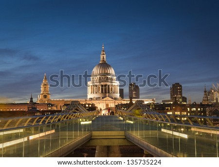 Pretty night time illuminations of St Paul's Cathedral and the millennium bridge along the river Thames.