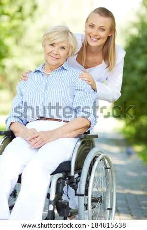 Pretty nurse and senior patient in a wheelchair looking at camera - stock photo