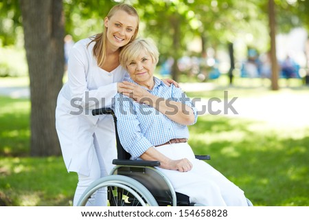 Pretty nurse and senior patient in a wheelchair looking at camera outside - stock photo