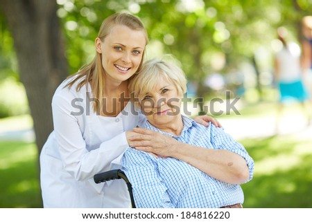 Pretty nurse and senior patient looking at camera outside - stock photo