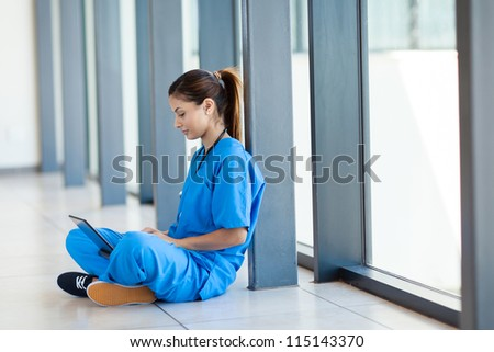 pretty nurse sitting on floor and using laptop computer during break - stock photo
